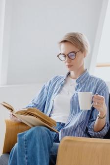 Une jeune femme européenne aux cheveux blonds courts boit du café ou du thé et lit un livre