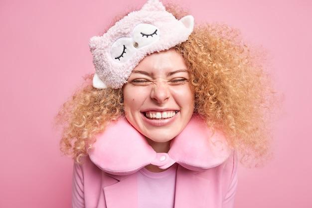 Jeune femme européenne aux cheveux bouclés positif sourit largement