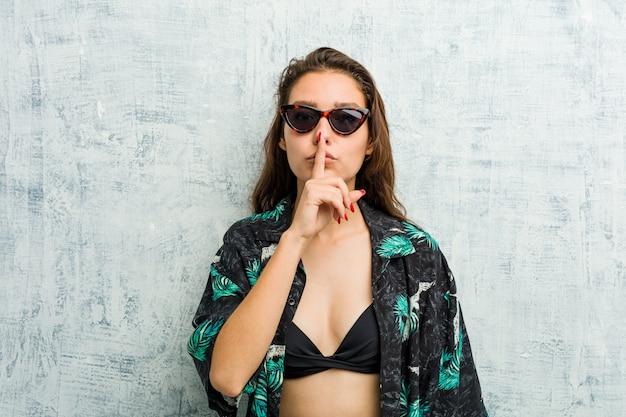 Jeune femme européenne en bikini gardant un secret ou demandant le silence.