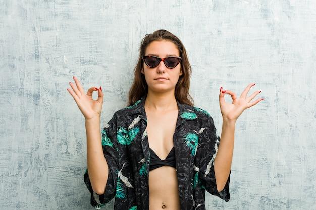 Jeune femme européenne en bikini se détend après une dure journée de travail, elle pratique le yoga.