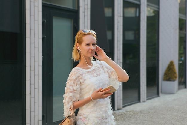 Jeune femme européenne blonde utilisant un smartphone en se tenant debout dans le quartier commerçant d'une ville, avec des fenêtres de maison sur fond moderne. porter des lunettes de soleil et un sac à main.