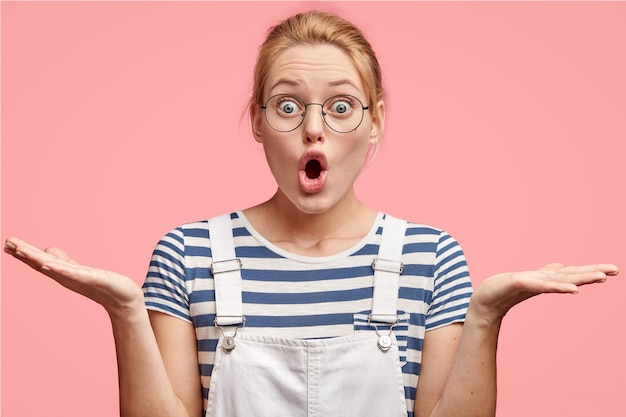Une jeune femme européenne embarrassée, perplexe, hausse les épaules, a une expression stupéfaite, ouvre largement la bouche
