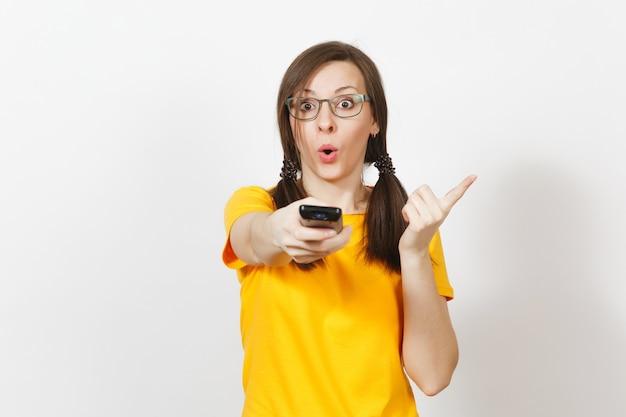 Une jeune femme européenne irritée et insatisfaite, un fan de football ou un joueur en uniforme jaune tient la télécommande de la télévision, s'inquiète de perdre une équipe isolée sur fond blanc. fan de sport, concept de mode de vie sain.