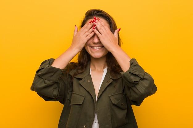 Jeune femme européenne isolée sur fond jaune couvre les yeux avec les mains