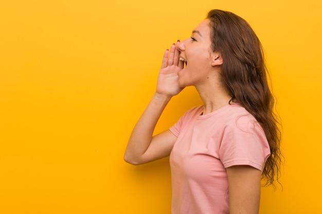 Jeune femme européenne isolée sur fond jaune en criant et en tenant la paume près de la bouche ouverte.