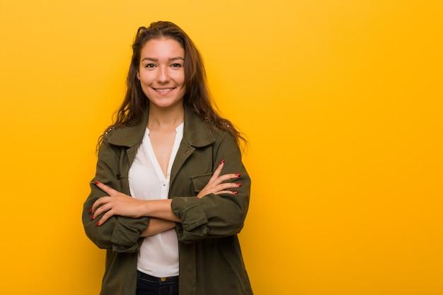 Jeune femme européenne isolée sur fond jaune qui se sent confiante, croisant les bras avec détermination.