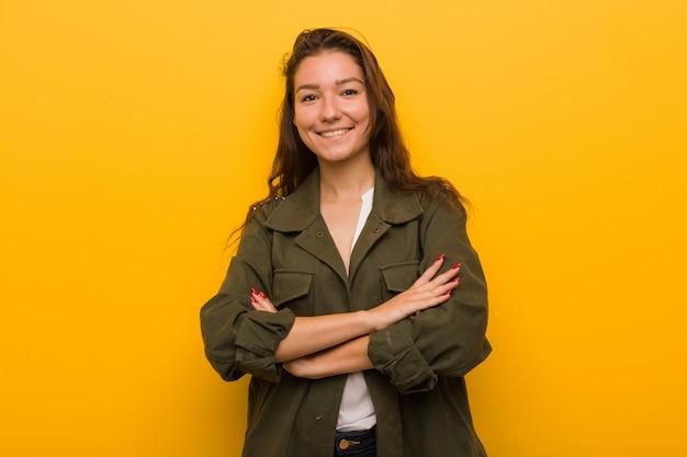 Jeune femme européenne isolée sur fond jaune souriant confiant avec les bras croisés.
