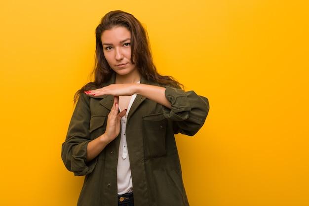 Jeune femme européenne isolée sur jaune montrant un geste de temporisation.