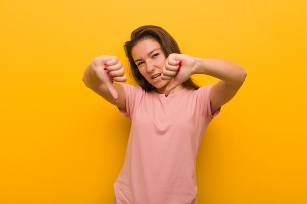 Jeune femme européenne isolée sur jaune montrant le pouce vers le bas et exprimant l'aversion.
