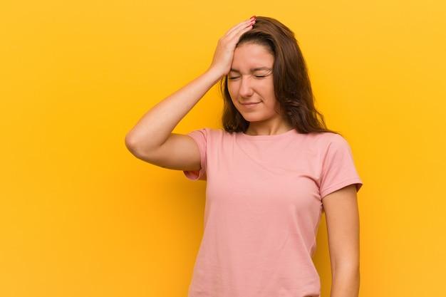 Jeune femme européenne isolée sur jaune en oubliant quelque chose, claquant le front avec palme et fermant les yeux.