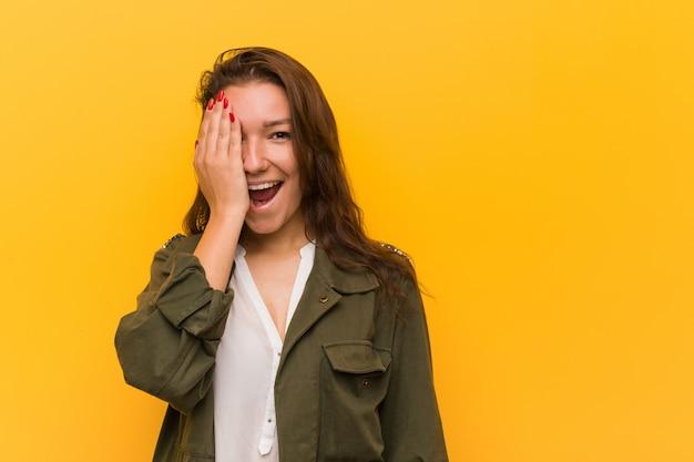 Jeune femme européenne isolée sur jaune s'amuser couvrant la moitié du visage avec palme.
