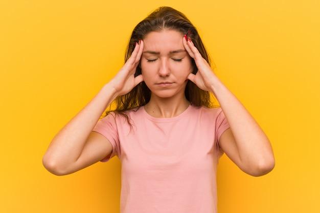 Jeune femme européenne isolée sur jaune touchant ses tempes et ayant des maux de tête.