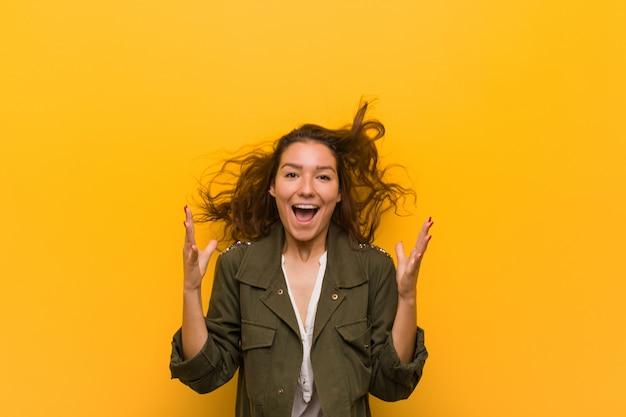 Jeune femme européenne isolée sur mur jaune célébrant une victoire ou un succès