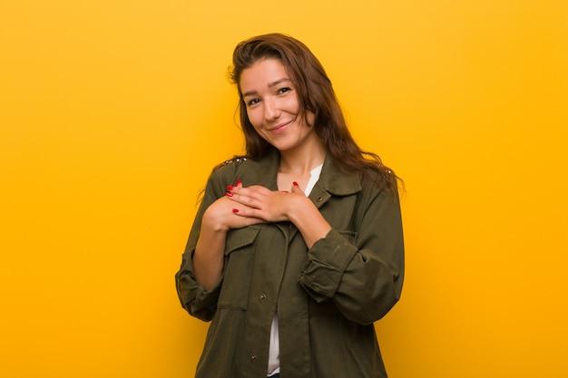 Jeune femme européenne isolée sur un mur jaune a une expression amicale, en appuyant la paume contre la poitrine. concept d'amour.
