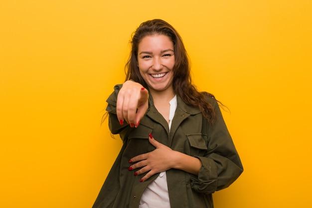 Jeune femme européenne isolée sur les points jaunes avec le pouce, riant et insouciant.