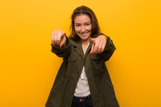 Jeune femme européenne isolée sur des sourires joyeux jaunes pointant vers l'avant.