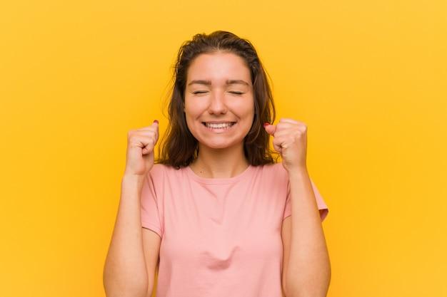 Jeune femme européenne levant le poing, se sentir heureuse et réussie. concept de victoire.