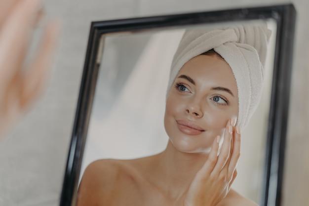 Jeune femme européenne nue touche la peau douce sur le visage se regarde dans le miroir de la salle de bain