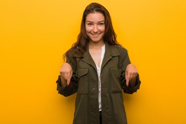 Jeune femme européenne pointe avec les doigts, sentiment positif.