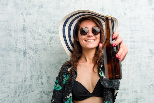 Jeune femme européenne portant un bikini et buvant une bière