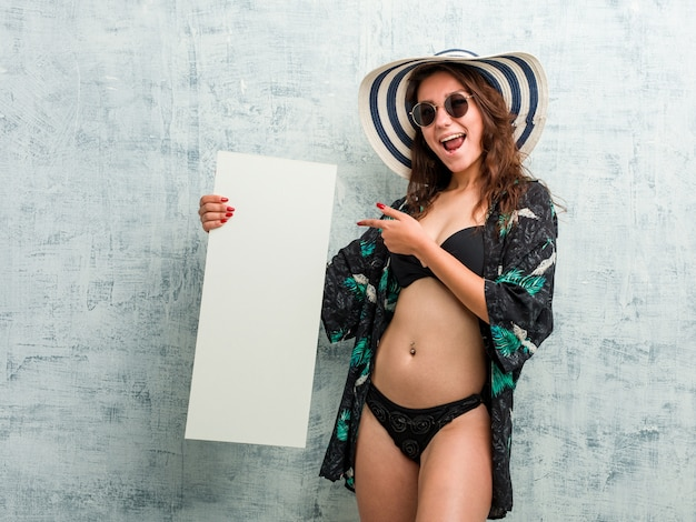 Jeune femme européenne portant un bikini et tenant une pancarte