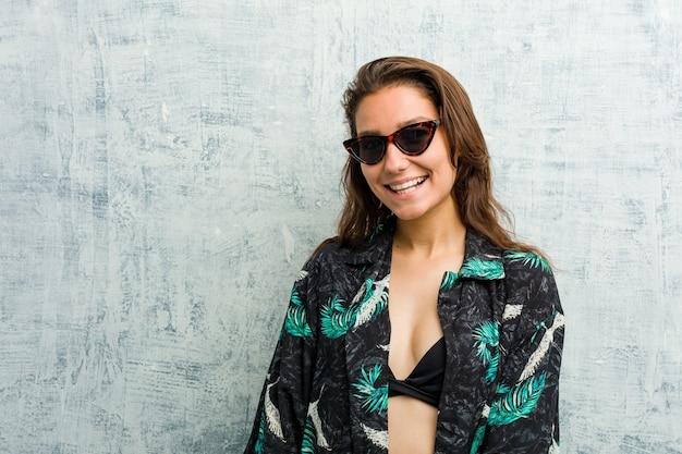 Jeune femme européenne portant un clin de œil bikini, drôle, amical et insouciant.