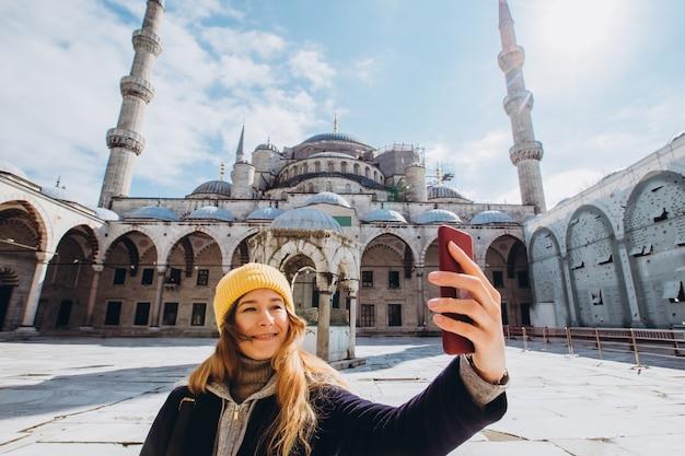 Jeune femme européenne prend un portrait selfie à istanbul, turquie. fille marche à travers l'hiver istanbul. blonde prend une photo au téléphone dans le contexte d'une mosquée en journée d'automne.
