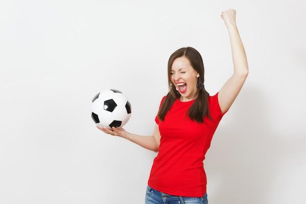 Jeune femme européenne ravie, deux queues de cheval amusantes, fan de football ou joueur en uniforme rouge tenant un ballon de football classique isolé sur fond blanc. santé du football sportif, concept de mode de vie sain.