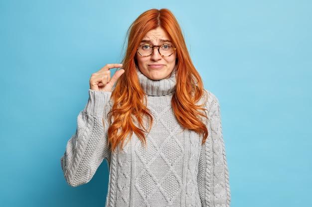 Jeune femme européenne rousse mécontente vêtue d'un pull d'hiver gris montre une petite quantité de geste montre une petite taille avec les doigts.