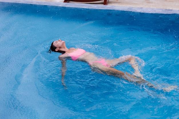 Jeune femme européenne slim fit heureux en piscine bleu bikini rose vif