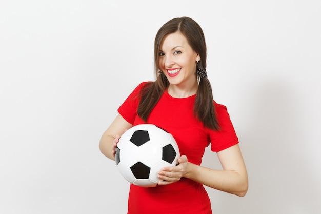 Jeune femme européenne souriante, deux queues de cheval amusantes, fan de football ou joueur en uniforme rouge tenant un ballon de football classique isolé sur fond blanc. sport jouer au football santé, concept de mode de vie sain.