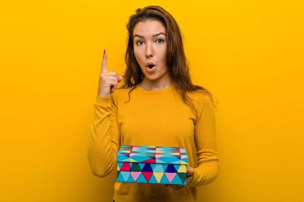 Jeune femme européenne tenant un cadeau ayant une excellente idée, concept de créativité.
