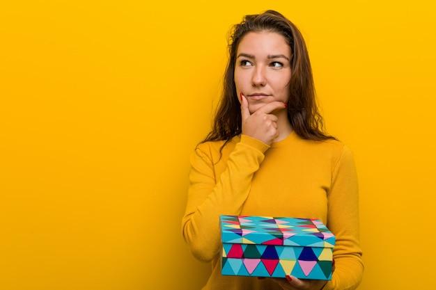Jeune femme européenne tenant un cadeau à côté avec une expression douteuse et sceptique.