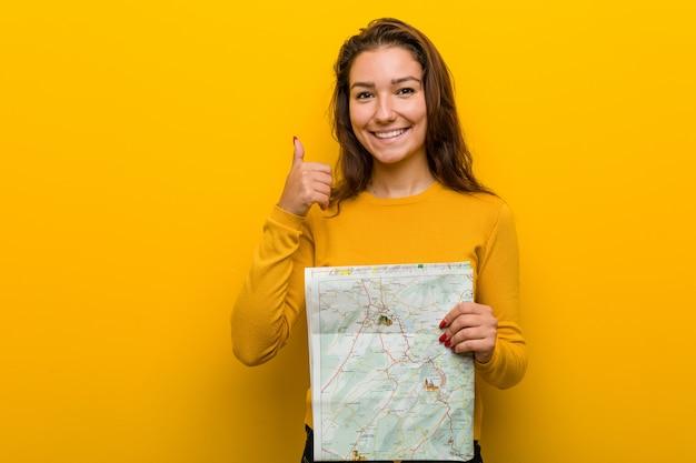 Jeune femme européenne tenant une carte souriante et levant le pouce vers le haut