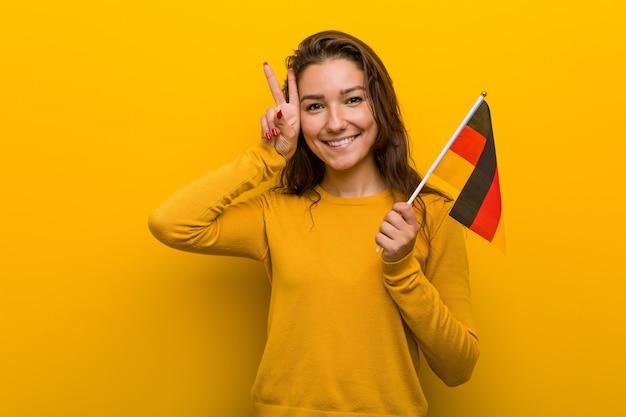 Jeune femme européenne tenant un drapeau de l'allemagne montrant le signe de la victoire et souriant largement.