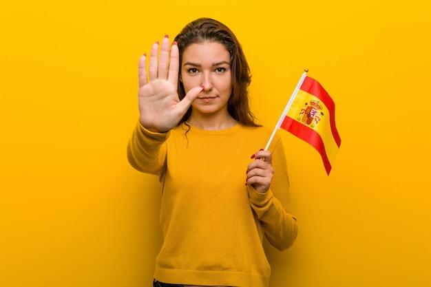 Jeune femme européenne tenant un drapeau espagnol debout avec la main tendue montrant le panneau d'arrêt, vous empêchant