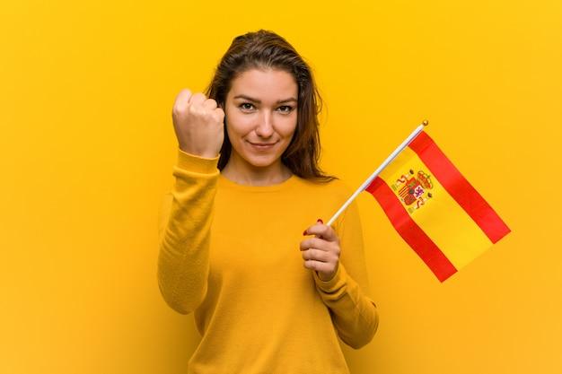Jeune femme européenne tenant un drapeau espagnol montrant le poing à la caméra, une expression faciale agressive.