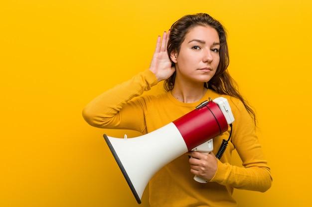 Jeune femme européenne tenant un mégaphone essayant d'écouter un commérage