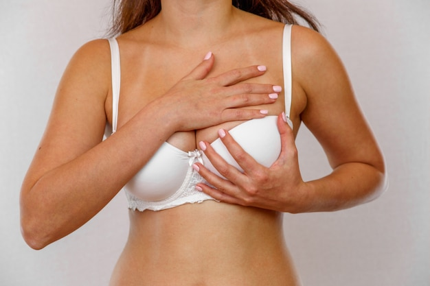 Jeune femme examine son sein pour le cancer sur blanc