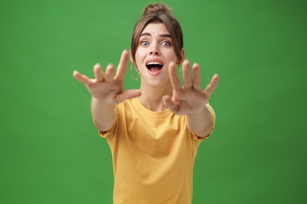 Une Jeune Femme Excitée Et Accro à L'air Goog, Tend Les Mains Vers La Caméra Avec Un Regard Imprudent Voulant Saisir Quelque Chose Qu'elle Désire Voir Ce Qu'elle Voulait Depuis Longtemps Sur Un Mur Végétal. Photo Premium