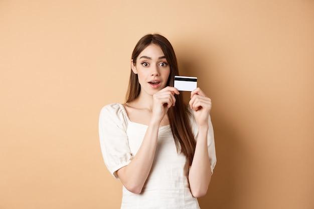 Jeune femme excitée montrant une carte de crédit en plastique et regarde émerveillée par la caméra debout sur fond beige