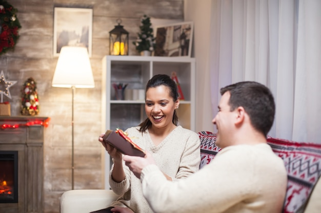 Jeune femme excitée pendant que son mari lui offre un cadeau tout en célébrant noël.