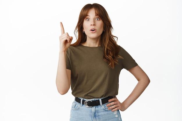 Jeune femme excitée suggérant un plan, levant le doigt vers le haut, haletant et semblant surprise, étonnée par la publicité vers le haut, debout sur blanc.