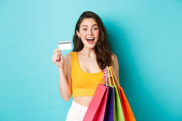 Jeune femme excitée tenant des sacs à provisions et montrant une carte de crédit en plastique, achetant des choses pendant les offres promotionnelles, debout sur fond bleu.