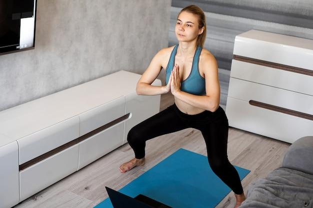 Jeune femme exerçant et faisant des squats.