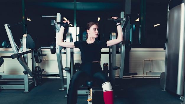 Jeune femme exerçant sur la machine de presse d'épaule