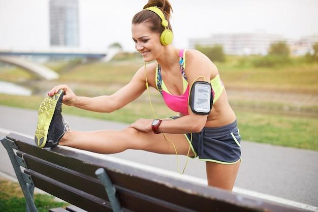 Jeune femme exerçant en plein air. le banc est une aide précieuse lors de l'étirement