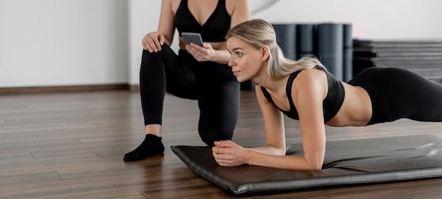 Jeune femme exerçant à la salle de sport faisant une planche