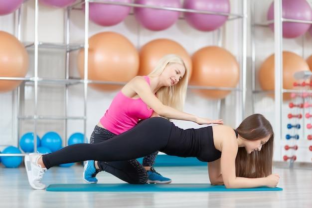 Jeune femme exerçant avec son instructeur de conditionnement physique