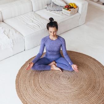Jeune femme exerçant le yoga dans le salon, se détendre avec la méditation d'yoga à la maison.